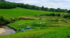 tents pitched by a stream