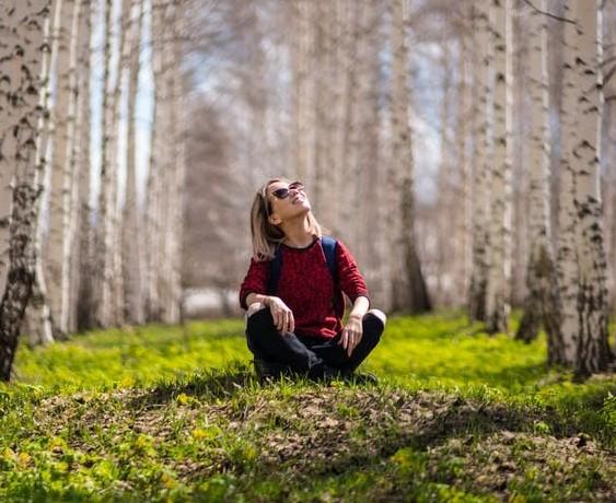 woman sitting amongst trees