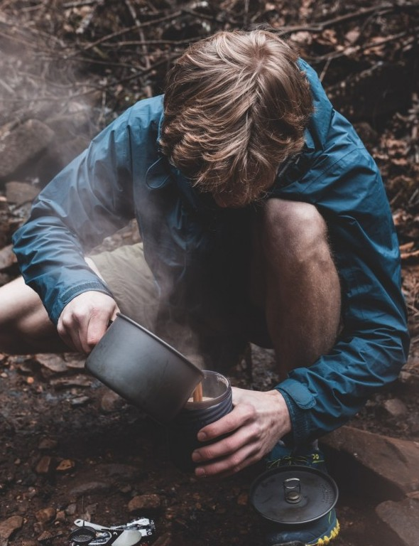 Teenage boy making tea while camping