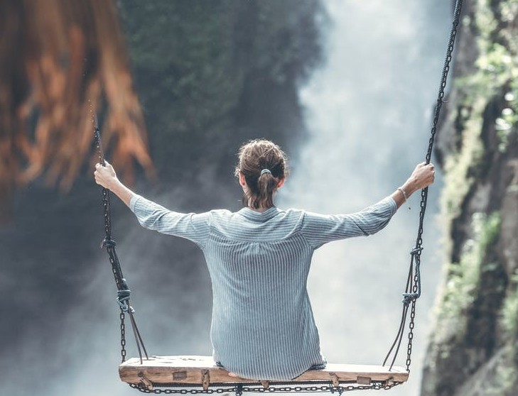 woman on large swing overlooking waterfall