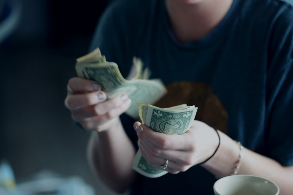 A woman counting her cash for her business budget