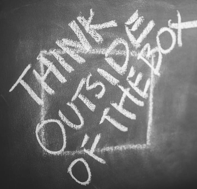 This is a picture of a black board with the words think outside the box