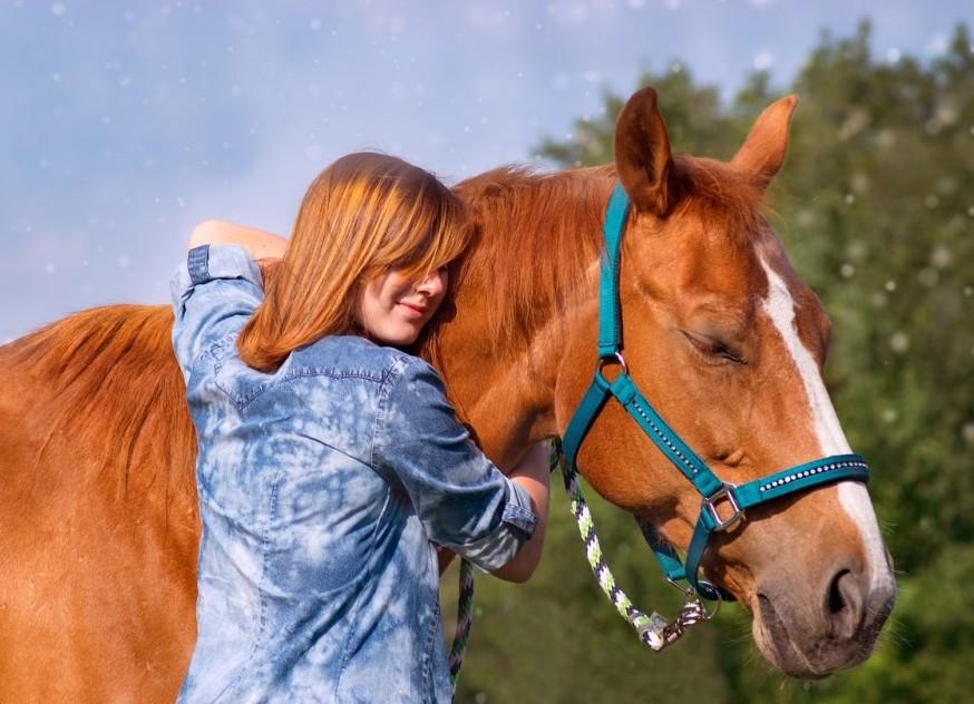 Lady hugging horses neck