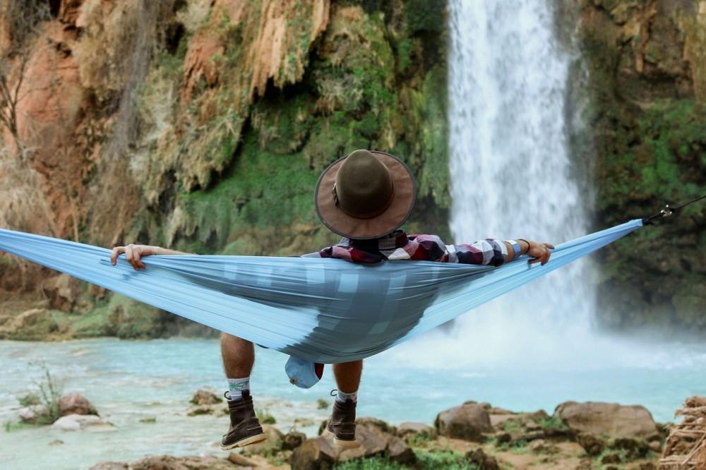 Man in hammock relaxing by waterfall