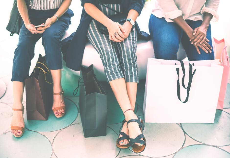 Three ladies with shopping bags sitting down
