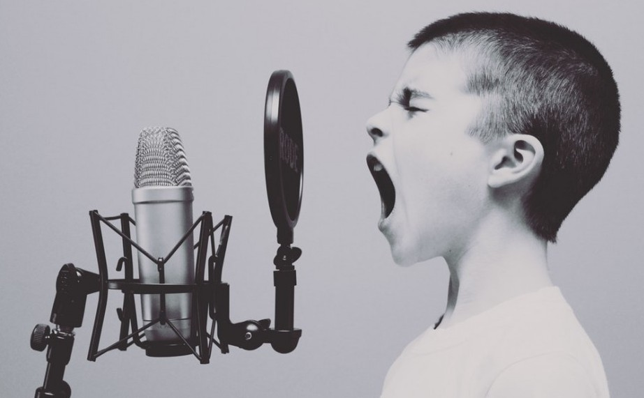 a boy shouting into microphone