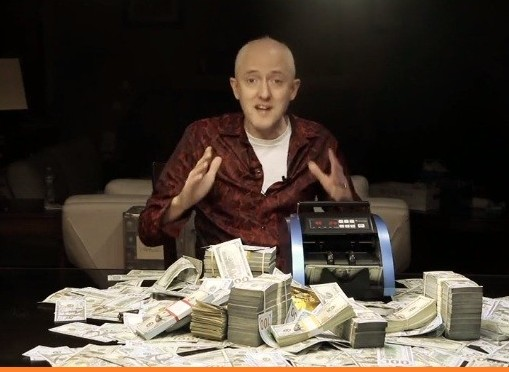 owner of profit injector sitting at the table with the money counting machine and stacks of cash on the table