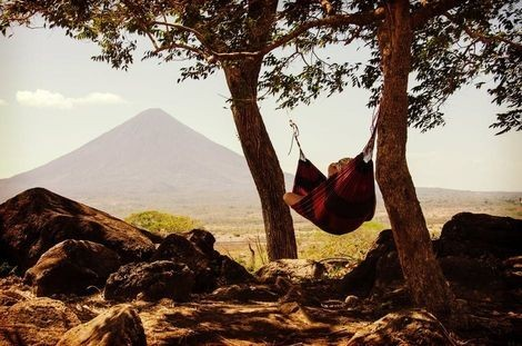 Person relaxing in a hammock near a mountain range.