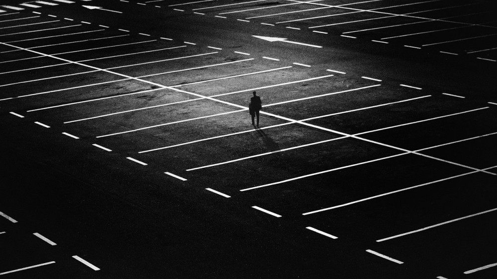 A man standing on an empty large parking lot
