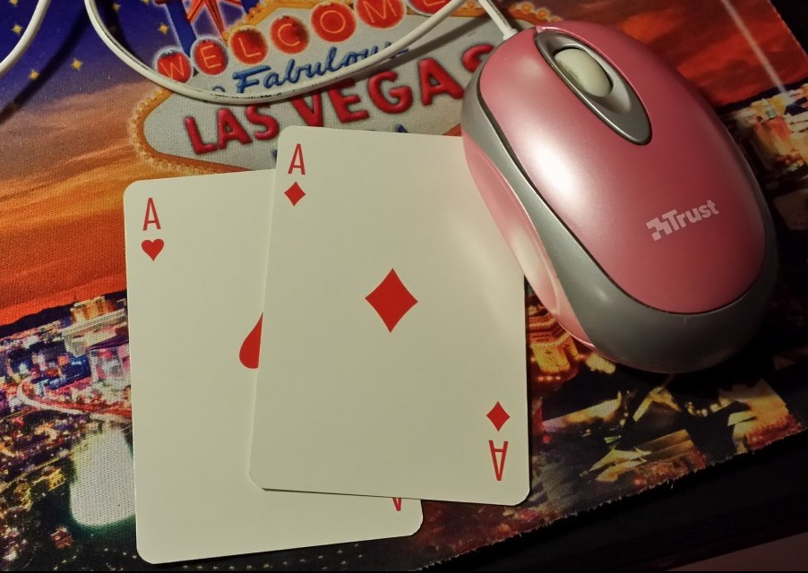 two playing cards ace of hearts and ace of diamonds and a pink computer mouse on a las vegas mouse pad