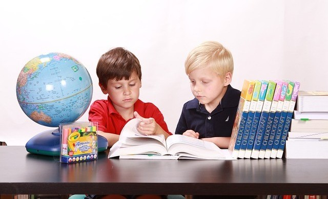 Two six year old boys figuring out how to read