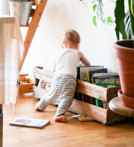 Toddler searching for a book to read
