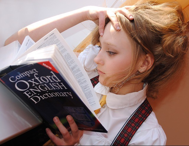 Girl figuring out how to learn english for speaking using dictionary