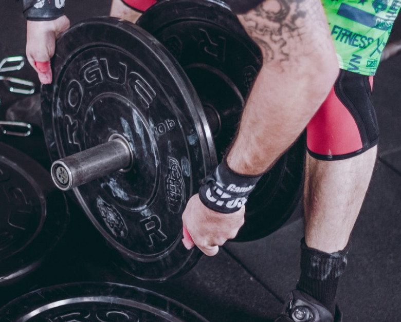 Man adding plates to barbell