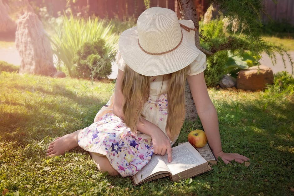 Young girl reading a book on grass