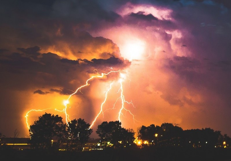 Colorful lightnings striking over trees
