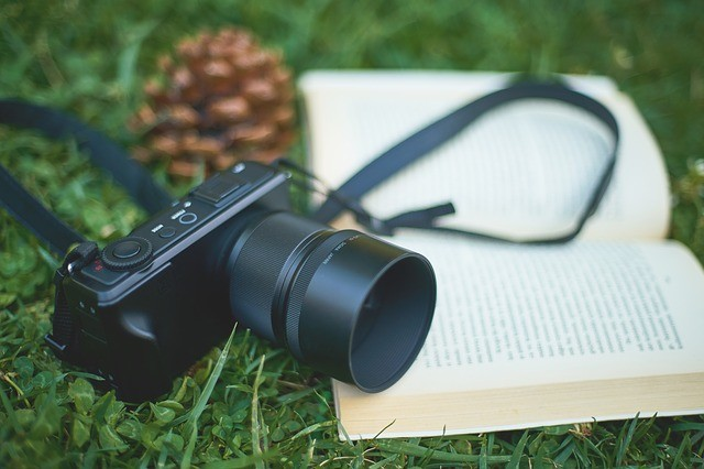 Camera and book lying on the grass