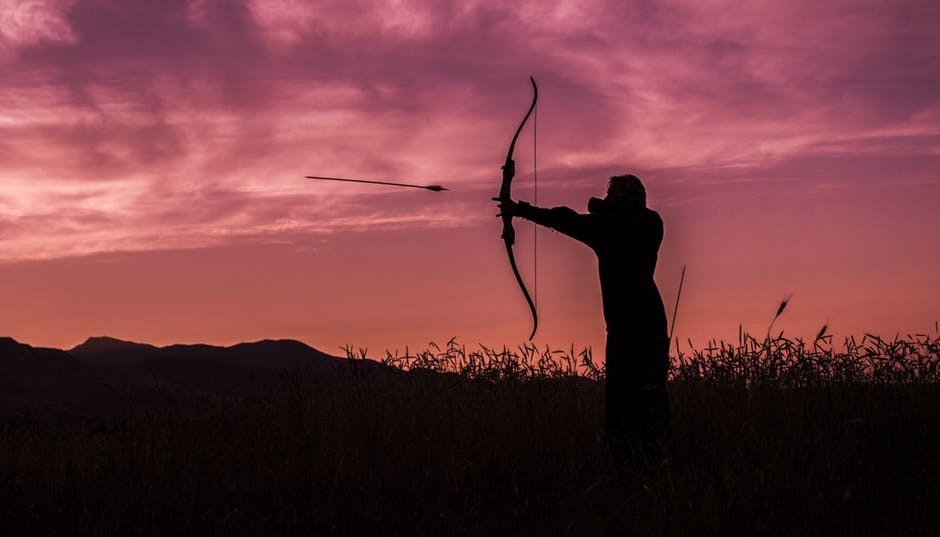 Person throwing arrows with bow