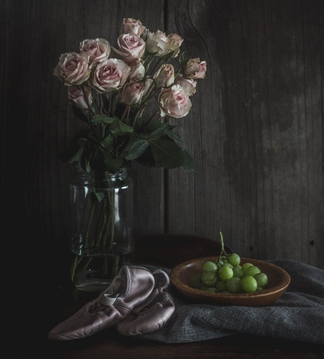 Vase of flowers, ballet shoes and a plate with grapes