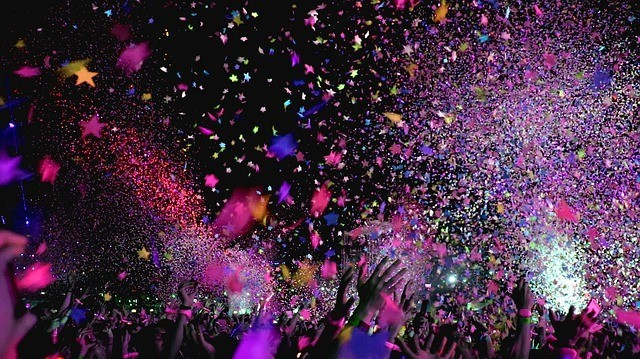 People celebrating and colourful star-shaped papers thrown in the air