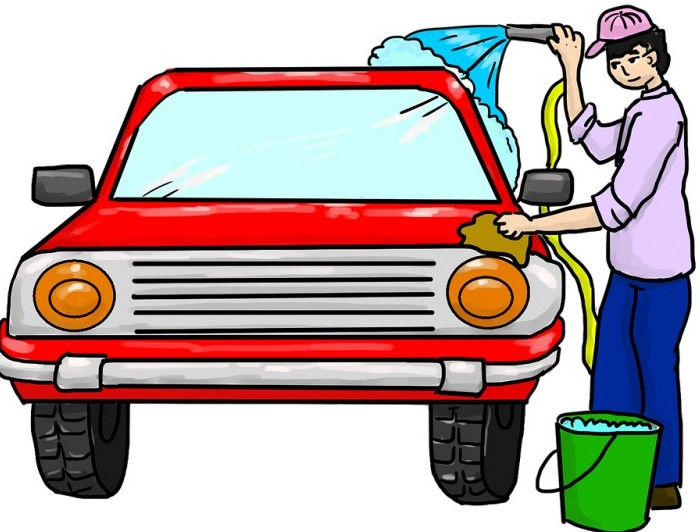 Making Your House Peaceful | Household Chore List | A teenager in a baseball cap sprays a car with a water hose and rubs it with a cleaning cloth.