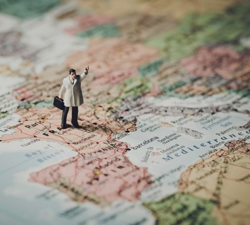 A tiny tourist figurine stands on a map of Europe
