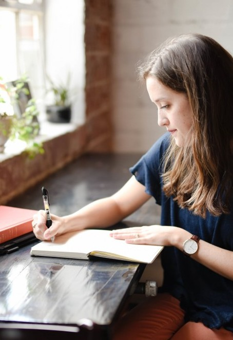 Creative Writing Process Steps - Your Finished Product. A young lady writes in a book while sitting at a table. Photo by hannah-olinger-549282-unsplash