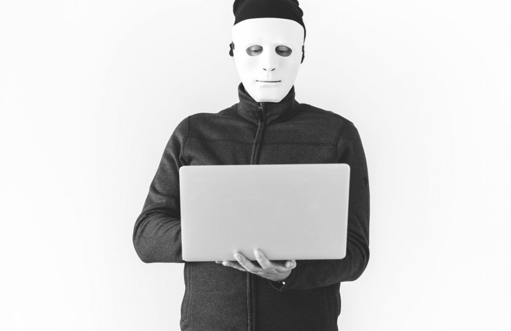 Man hiding his face with mask,standing holding an open laptop