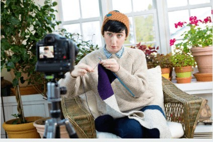 Woman sitting in front of camera demonstrating how to crochet