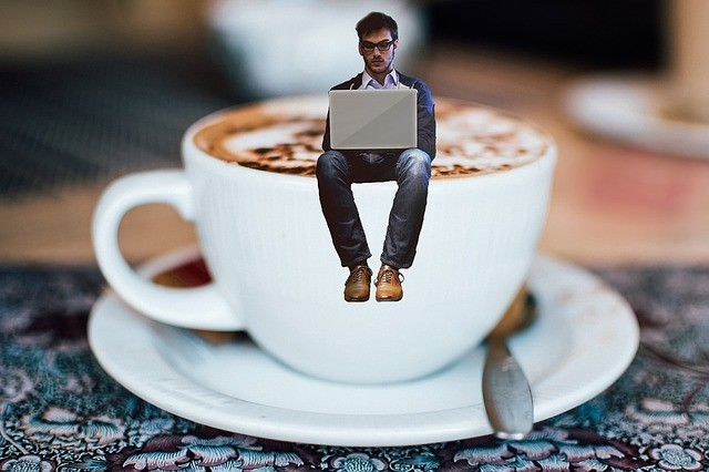 Funny illusion of a man sitting on a cup of coffee while typing on laptap