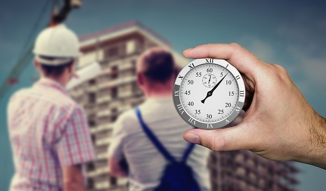 A Hand holding a timer clock with 2 workers in the background