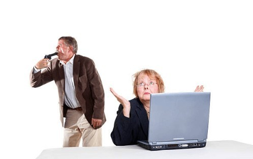 Frustrated Old Couple - Man standing with pistol pointed to his mouth, frustrated Lady sitting in front of laptop - When Should You Start Planning Retirement