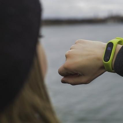 Girl wearing fitness yellow fitness tracker