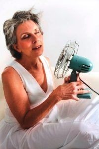 hot flashes- woman pointing a fan to her face