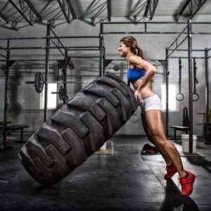 Woman lifting a big tire HIIT training