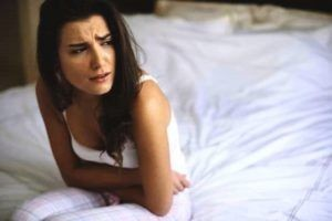 pms woman showing pain sitting on her bed
