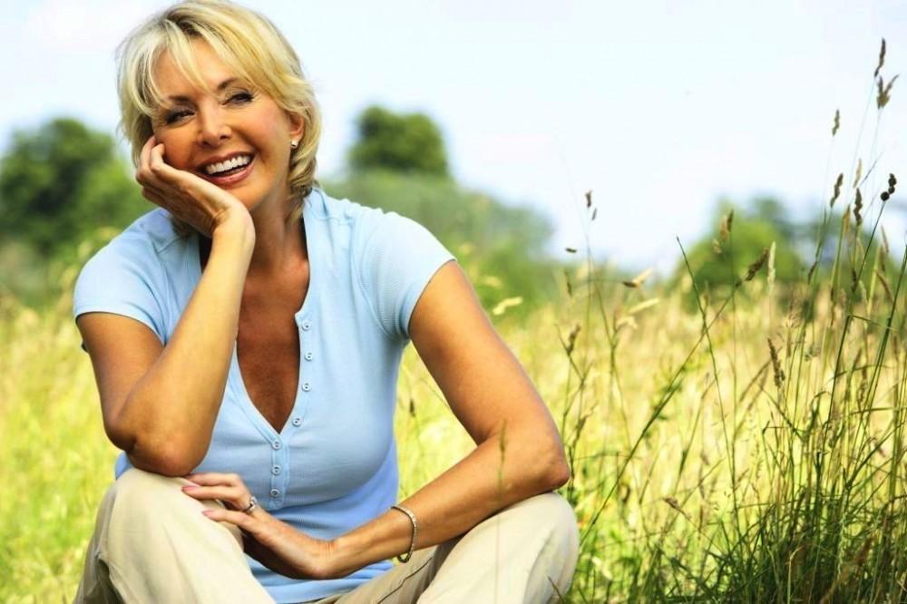 Woman in good mood sitting in a flower field