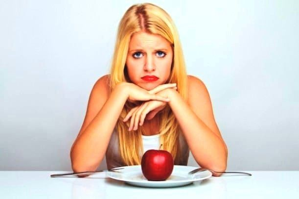A low-calorie diet (woman with one apple on her plate)
