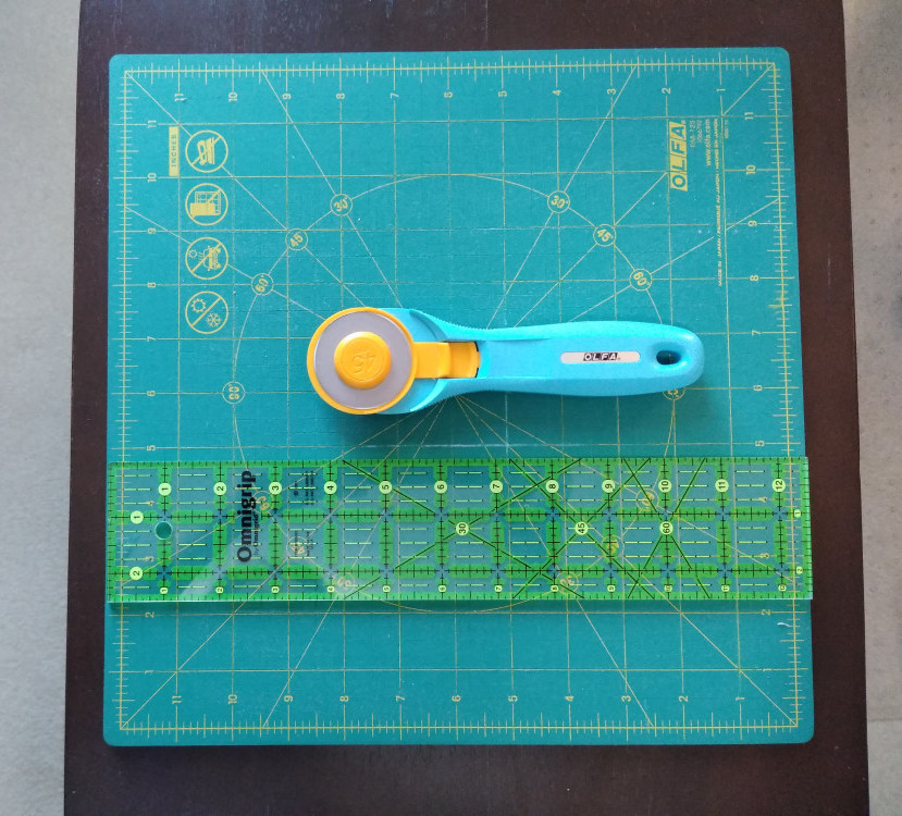 The top 3 items needed for making a quilt: 12' rotating cutting mat, 2 1/2' x 12' ruler and #45 rotary cutter placed on small brown table top