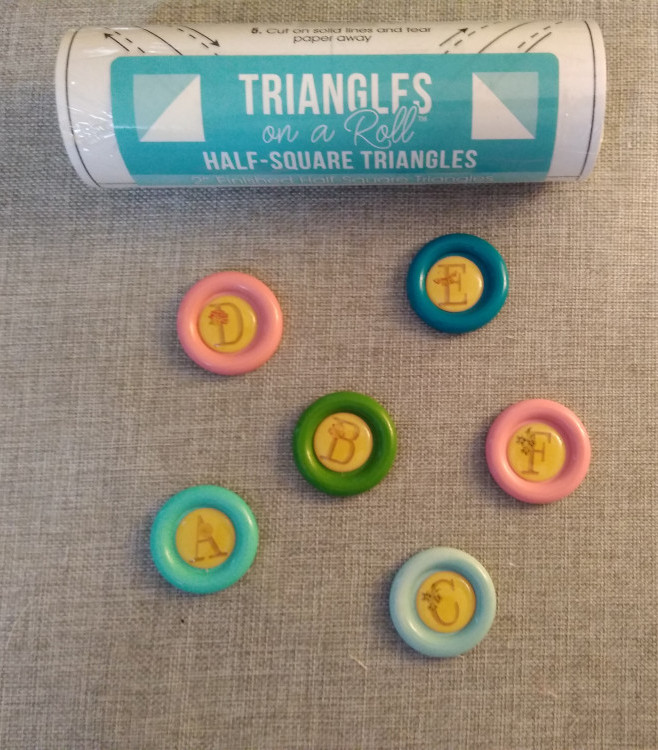 Roll of paper half-square triangles on a roll and buttons with alphabet stickers