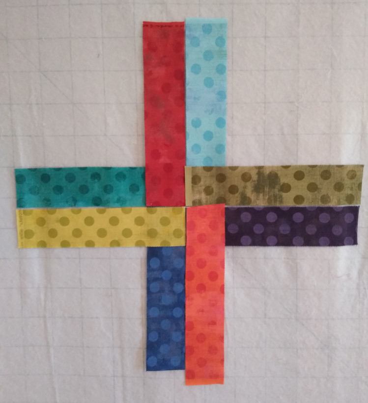 Place of pre cut jelly roll fabric strips in preparation for piecing Rising Star quilt top