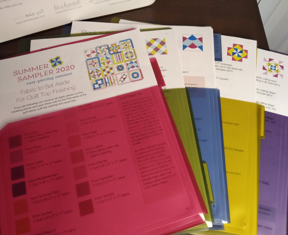 Multi colored pocket dividers for three ring binders used to hold copies of instructions for quilt blocks