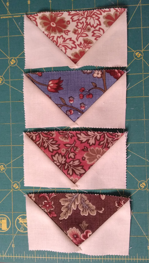 Fabric flying geese units on a rotating cutting mat