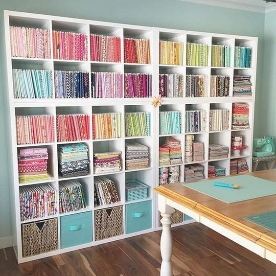 White open shelves used for storing colorful quilt fabric