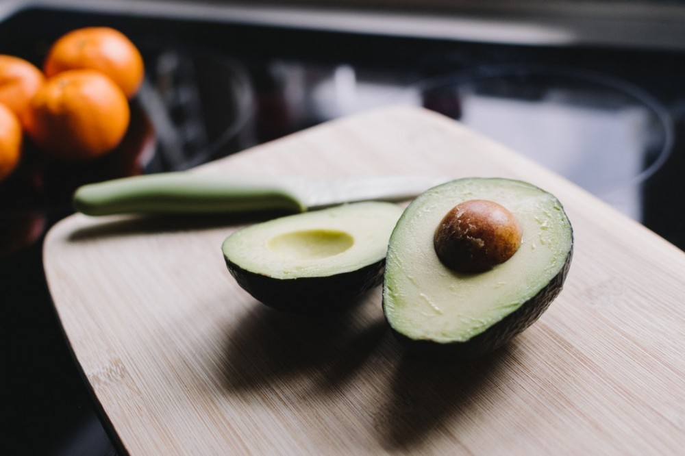 an avocado sliced in half on a chopping board with the stone still in the middle.