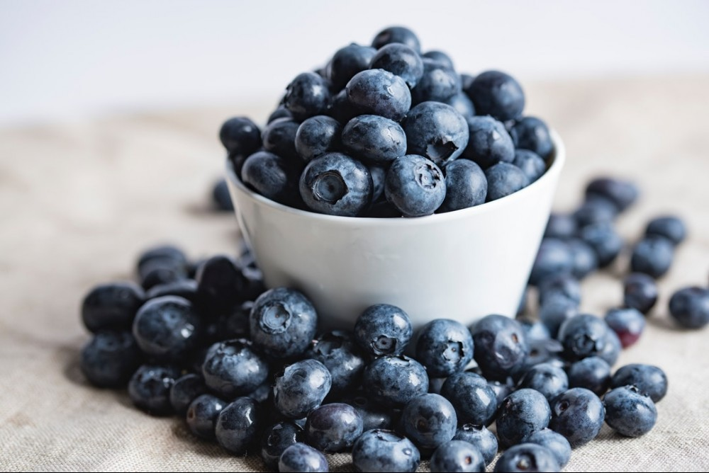 a white bowl that is overflowing with blueberries, they have spilt over on to the surface the bowl sits on.