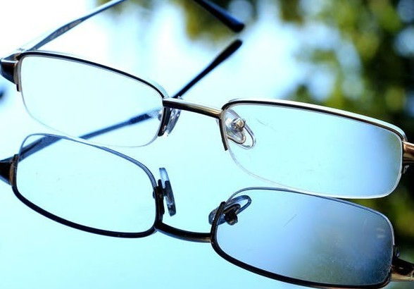 A pair of eye glasses on a glass table