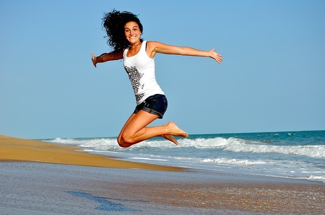 how to create a positive environment by removing negative people from your life, girl jumping on the beach