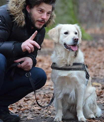 Man talking to labrador dog with leash in hand