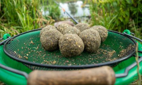 Carp Fishing with Groundbait -  Balls of groundbait over bucket with riddle